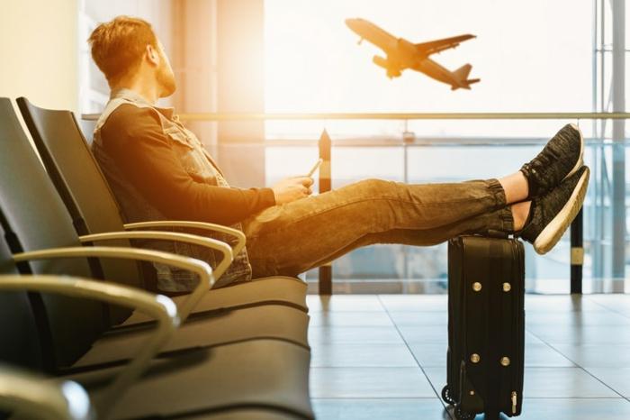 jeune homme, valise noire, salle d attente, fenêtre et avion qui s'envole, prendre les transports