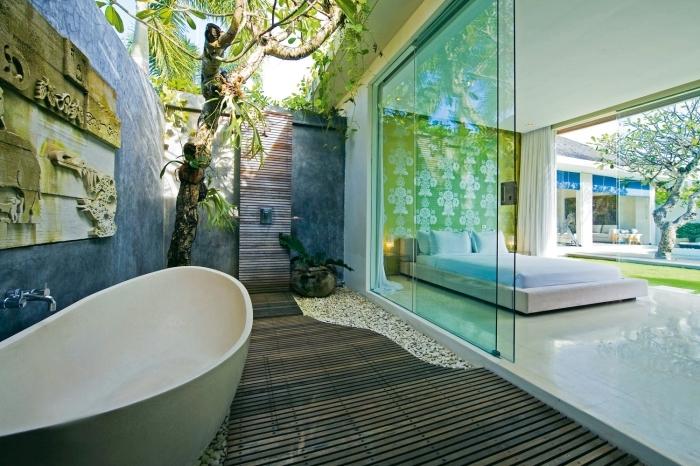 aménagement de salle de bain dans la cour arrière avec murs à peinture à effet béton et receveur de douche rectangulaire en bois