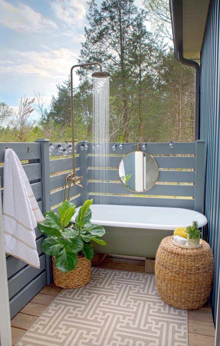 aménagement véranda en salle d'eau, déco terrasse en bois avec douche pluie en métal et baignoire autoportante