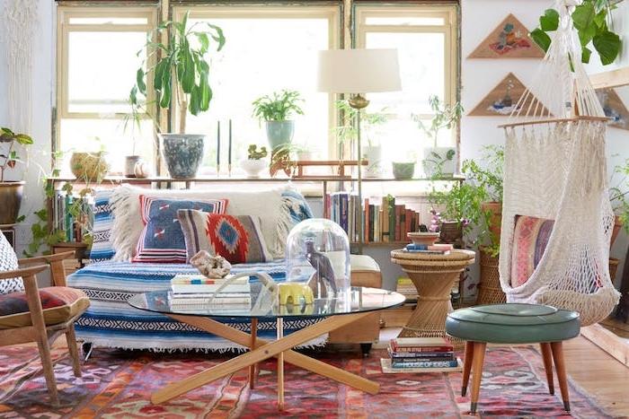 tapis oriental, balancelle d intérieur, table bois et verre, canapé décoré de couverture et coussins décoratifs colorés, bibliothèque basses, plusieurs plantes vertes d intérieur
