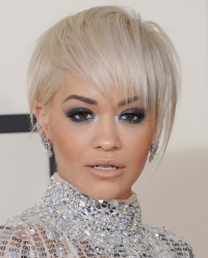 idée coupe de cheveux courts tendance femme 2019, Rita Ora aux cheveux en coupe garçon avec frange longue en blond polaire
