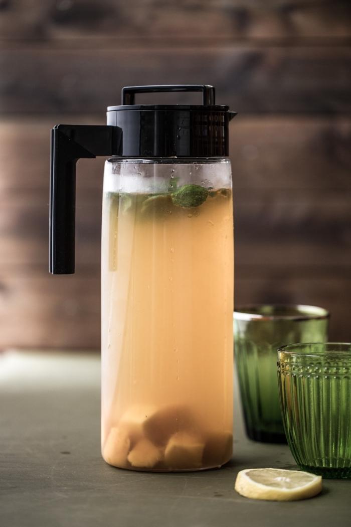 bouteille en verre remplie de thé vert refroidi aux fruits et feuilles de menthe, idée boisson froide saine aux fruits