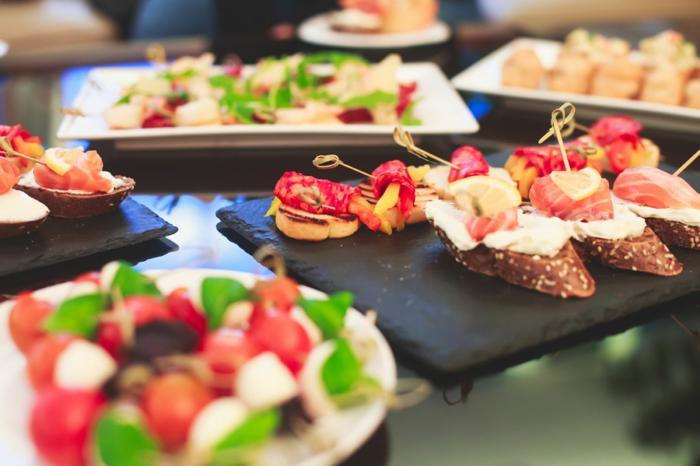 bruschettas de pin complèt, saumon fumé, fromage de chèvre, brochettes de tomates cerises et fromage, assiettes ardoises