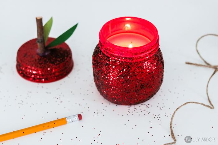 bougie diy à motif pomme fabriquée dans un pot en verre repeint de rouge et décoré à paillettes avec couvercle à branche et feuilles de papier vert