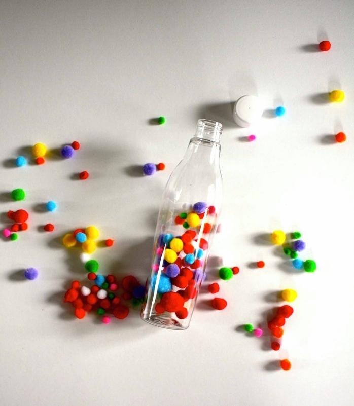 comment faire un jouet montessori, modèle de bouteille en verre à remplir avec petits pompons colorés pour faire un jouet bébé