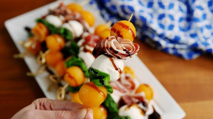 boules de melon et prosciutto, brochettes originales, sauce, feuille d épinard, assiette de service blanche
