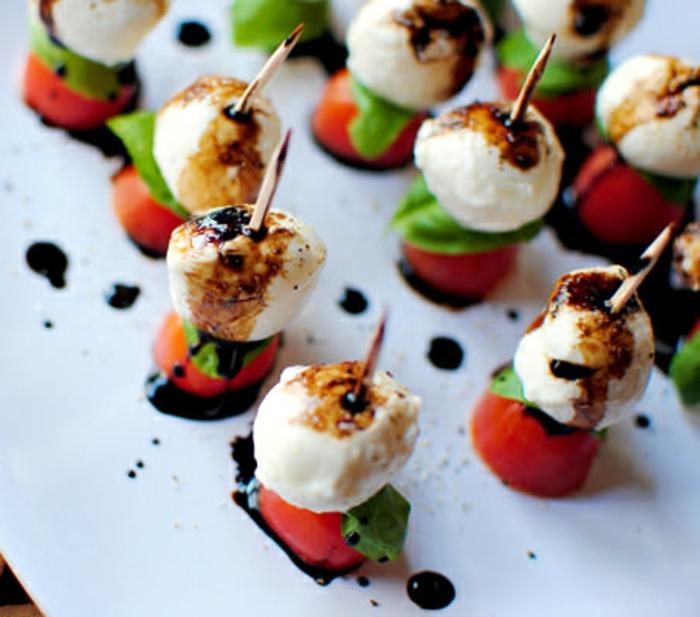 canapé de tomates et boules de fromage de chèvre à la sauce garni de feuille d épinards, assiette de service blanche