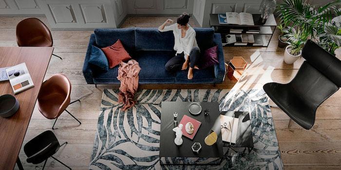 Femme assoit sur un canapé grand confortable à couleur bleu sombre, coussin boheme, déco berbère, aménagement chambre