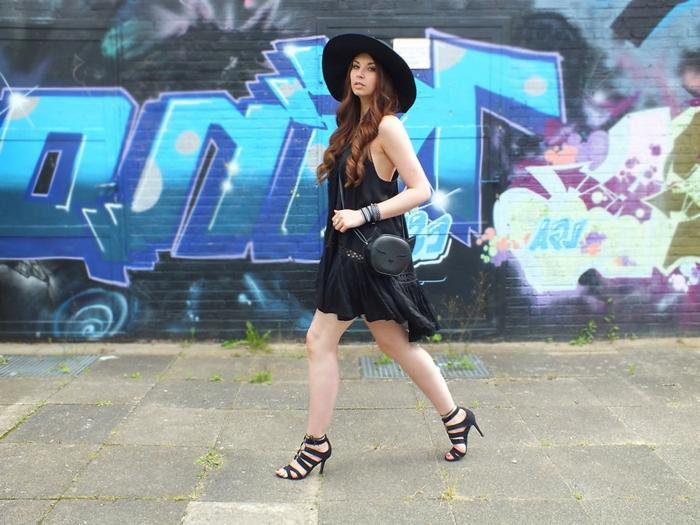 grande capeline noire, cheveux longs ondulants, longue jupe noire, sac rond noir, robe noire asymétrique