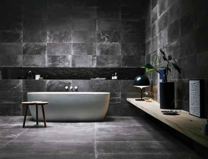 décoration salle de bain industriel aux murs et sol en gris anthracite avec baignoire blanche et étagère en bois clair