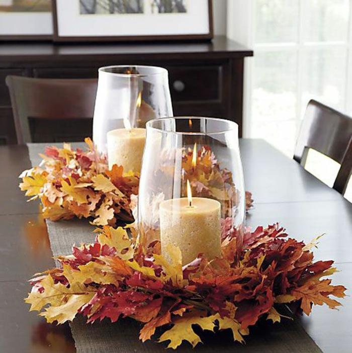 decoration de table chaleureuse, bougies allumées, feuilles d'automne arrangées, bougeoirs en verre simples