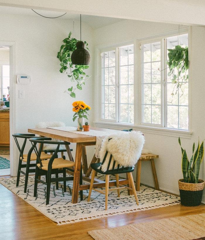 salle à manger contemporaine avec table bois brut, chaises bois et métal et tapis noir et blanc, sansevière en cache pot tressé et pots de plantes retombantes