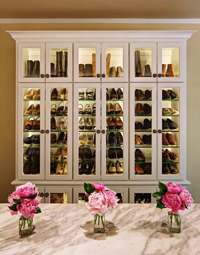 meuble de rangement chaussure dans une pièce dressing avec îlot central en marbre, grande armoire vitrine pour ranger ses chaussures de façon stylée