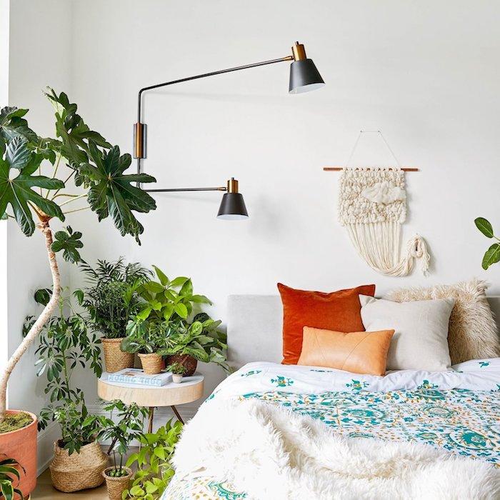 chambre jungle style boheme, macramé mural en guise de tete de lit, table de nuit rondin bois, chevet vert de végétation luxuriante, lampe originale