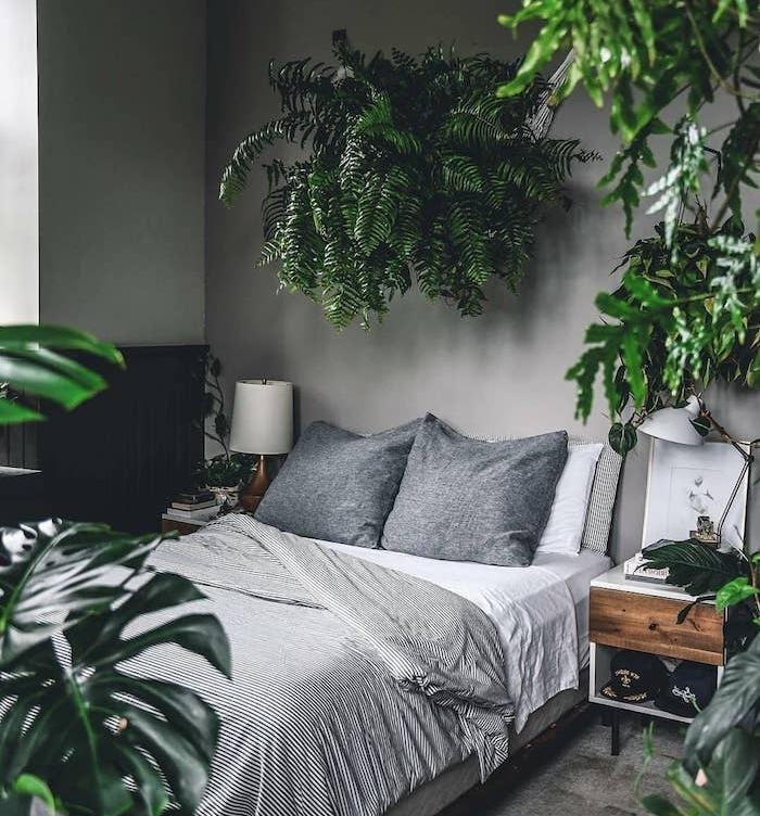chambre jungle deco en plusieurs plantes vertes, monstera deliciosa et plante en guise de tete de lit originale, linge maison gris et blanc, murs gris