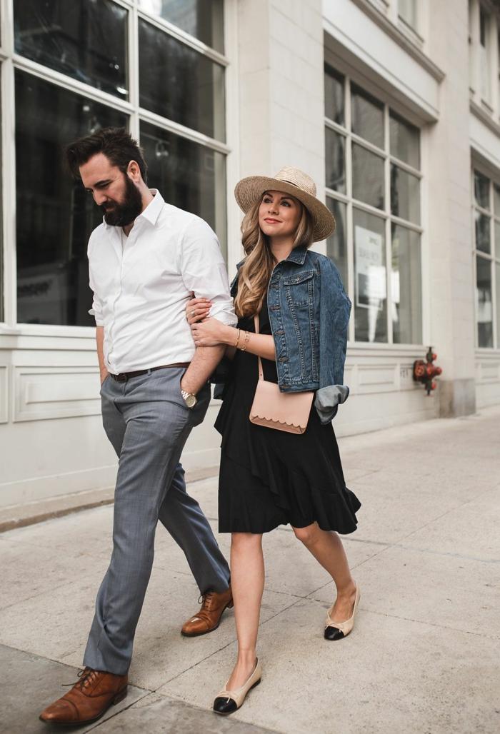 couple dans la rue, chapeau panama femme, robe noire fluide, sac épaule, veste en jean, homme chemise blanche