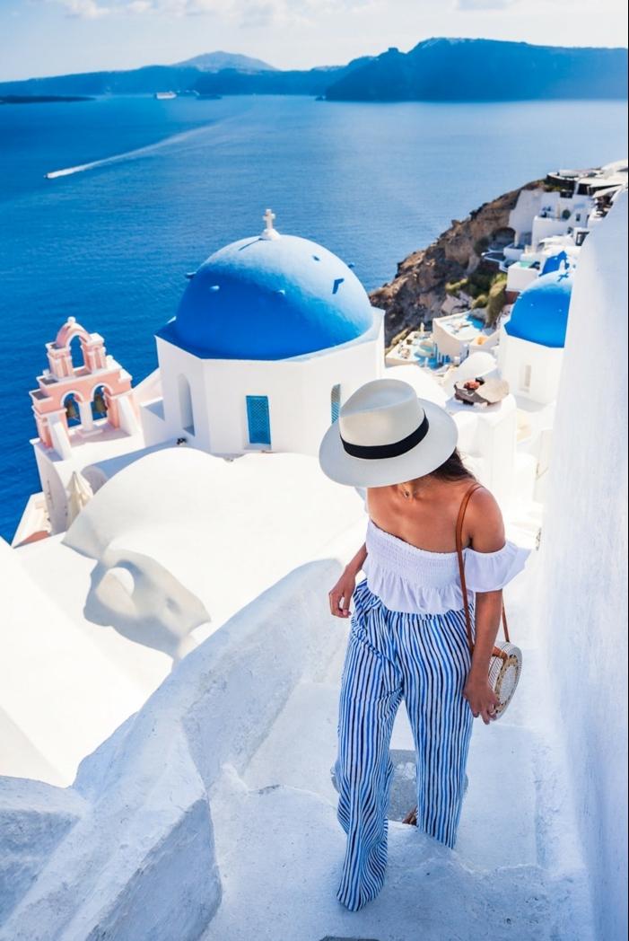 pantalon aux rayures verticales, nalade à Santorine, chapeau panama blanc, shirt off shoulders