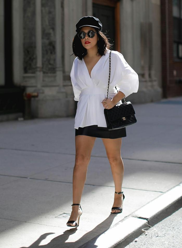 casquette porté avec une chemise blanche et jupe courte, sandales noires, lunettes de soleil rondes, sac laqué noir