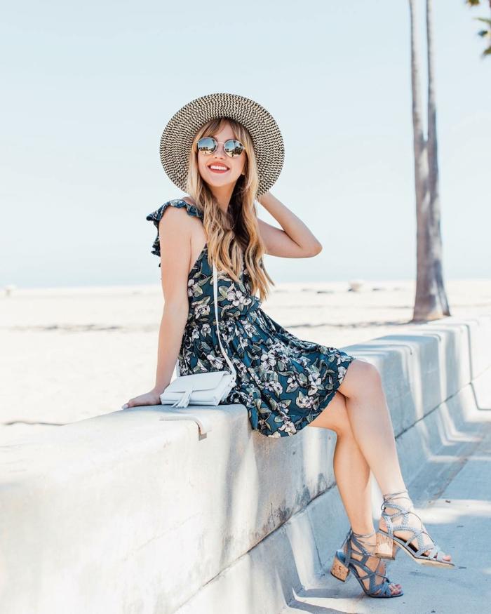 jeune femme assise à la bordure, capeline, robe bleue florale, sac épaule blanc, sandales bleues