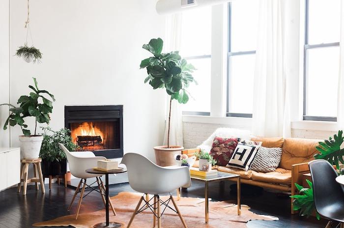 chaises scandinaves blanches, tapis peau animale, canapé bois et marron, table basse design, plantes en pots par sol, cheminée design