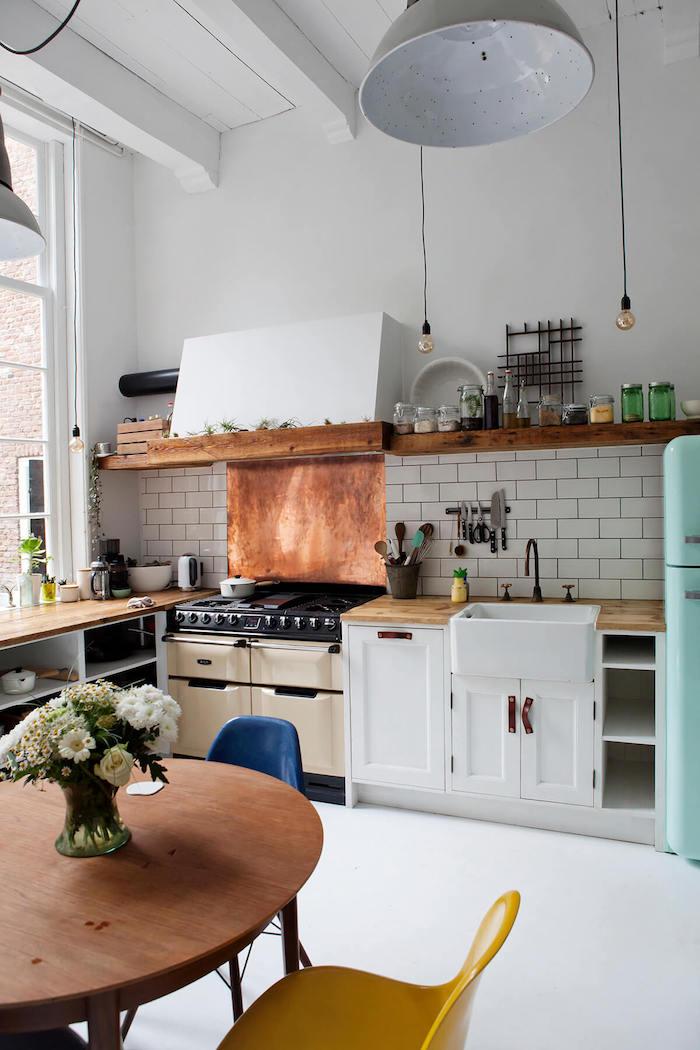 Cool petite cuisine avec coin table ronde chaises rétro à couleurs vintages, grande lustre, vase avec fleurs, aménagement cuisine petit appartement