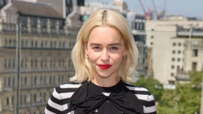 Emilia Clarke aux cheveux longs en coupe carré mi longs avec pointes légèrement ondulés et racines foncées