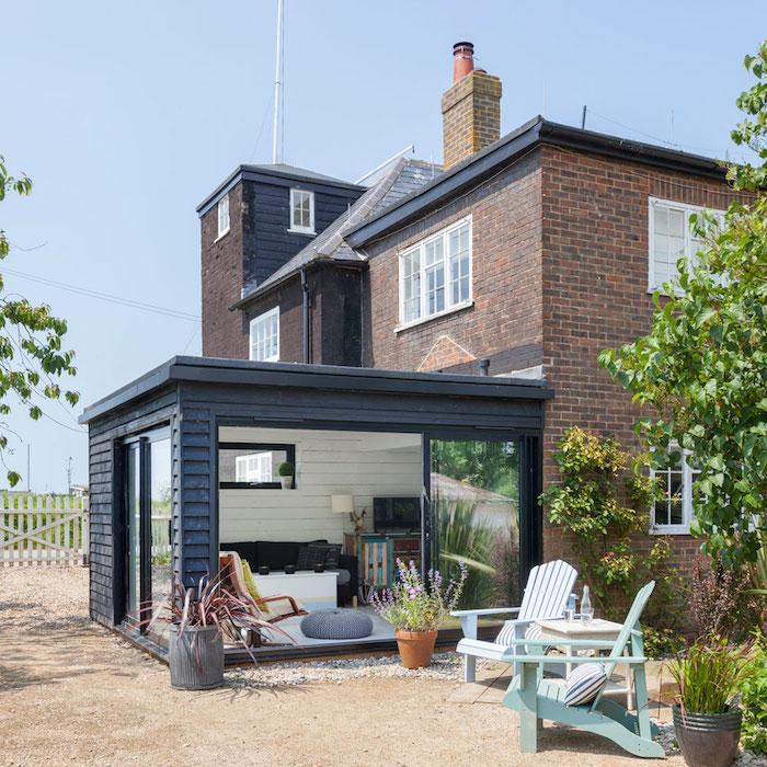 modele de maison de briques avec une veranda adossée en alu couleur noire, amenagement salon avec chaise longue, table basse et canapé gris sur véranda