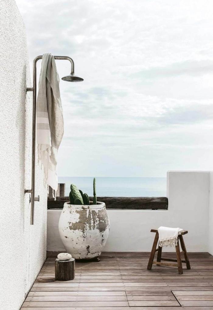 design minimaliste dans une salle de bain extérieure sur terrasse aux murs blancs et sol en planches de bois avec douche métal