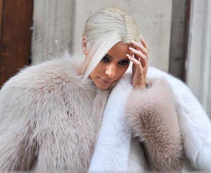 Kim Kardashian avec cheveux de couleur blond froid attachés en queue de cheval lisse basse avec mèches tombantes sur visage