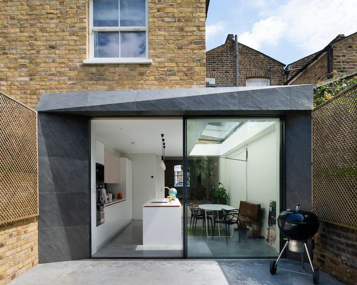 idee originale d extension maison grise à verrière extérieure, amenagement cuisine blanche et salle à manger en table et chaise metalliques