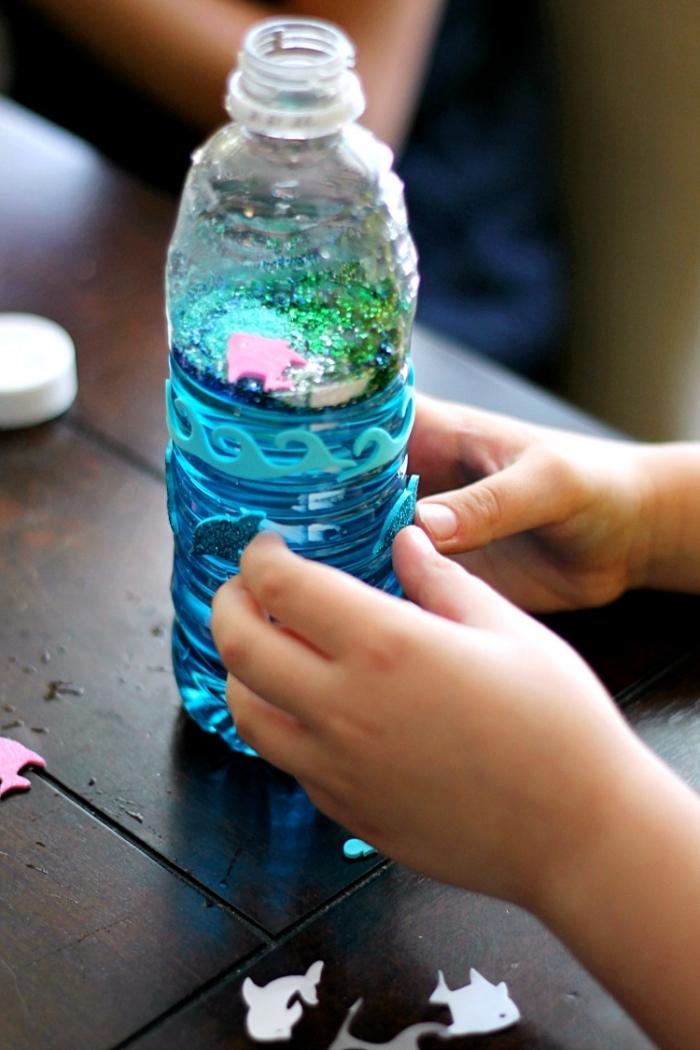 fabriquer des bouteilles sensorielles, modèle de bouteille Montessori sur thème fond de mer avec eau colorée et figurine animaux