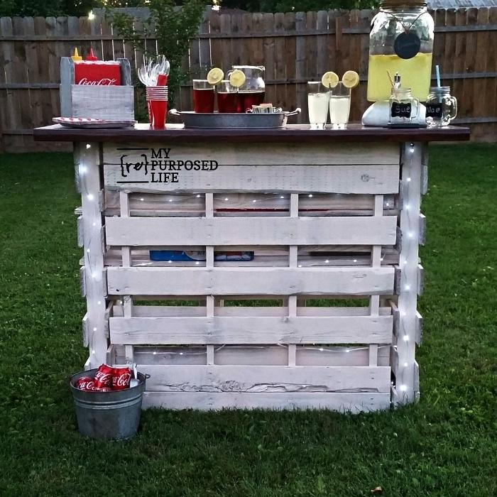 construire un bar en bois récup pour le jardin, bar à limonade en palette repeinte en blanc illuminée par une guirlande led