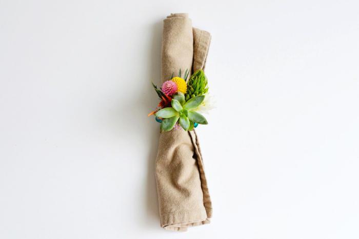 tissu en lin enroulé et décoré avec un anneau de serviette aux fleurs, deco a faire soi meme