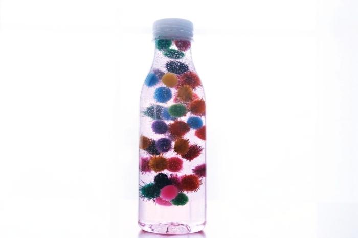 idée bouteille de retour au calme facile à réaliser, petite bouteille en verre remplie d'eau et de mini pompons colorés