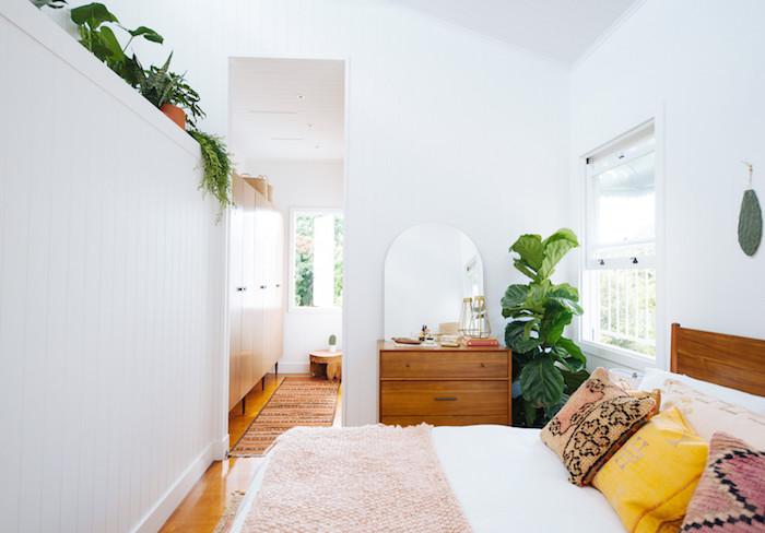 deco chambre boheme chic avec lit bois à linge blanc et plaid rose, coussins colorés, commode bois, murs blancs, plante verte en pot et végétation en hauteur