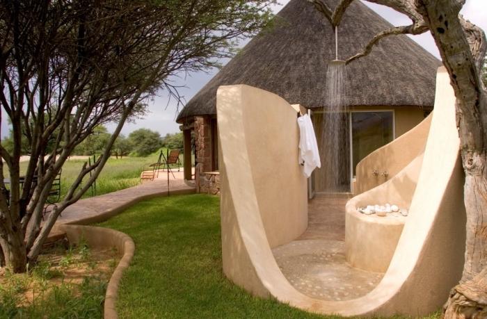 idée aménagement extérieur d'une maison avec petite salle de bain en pierre et douche fixe à effet pluie en inox