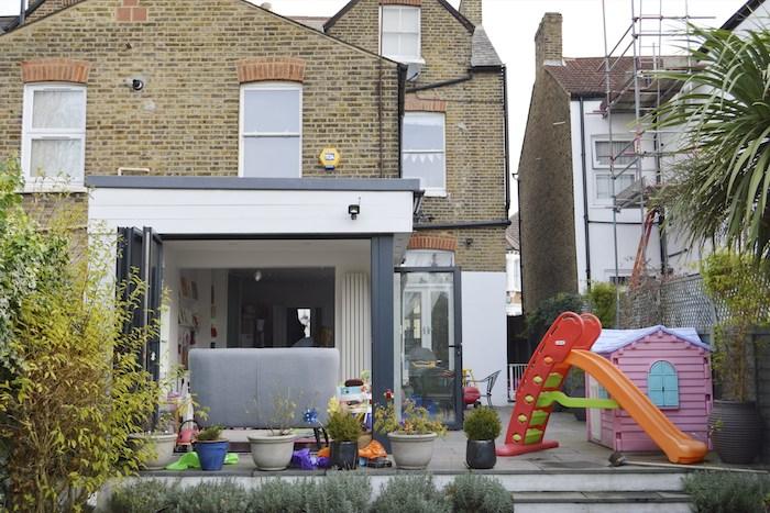 extension maison originale sur le coté d une maison de briques traditionnelle, ouverte sur jardin avec aire de jeux et plantes