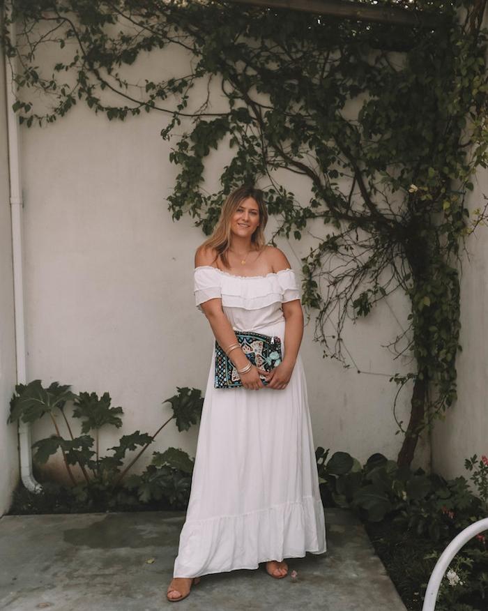 robe longue blanche à manches tombantes et volant, idée de robe d été fluide accessoirisé d une pochette colorée