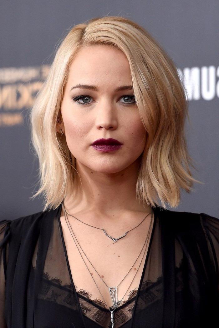 Jennifer Lawrence aux cheveux blonds en carré plongeant long avec raie de côté, coiffure cheveux effet wavy