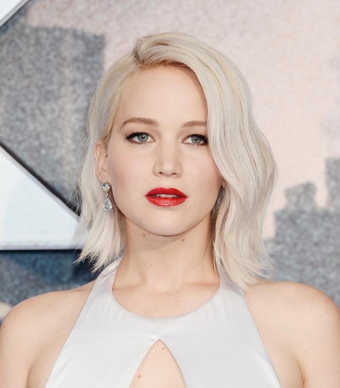 Jennifer Lawrence aux cheveux mi longs en carré plongeant de couleur blond blanc, coiffure facile cheveux mi longs