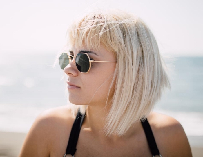 accessoires mode femme pour l'été, coupe de cheveux carré plongeant avec frange courte, modèle lunettes soleil tendance en noir et or,
