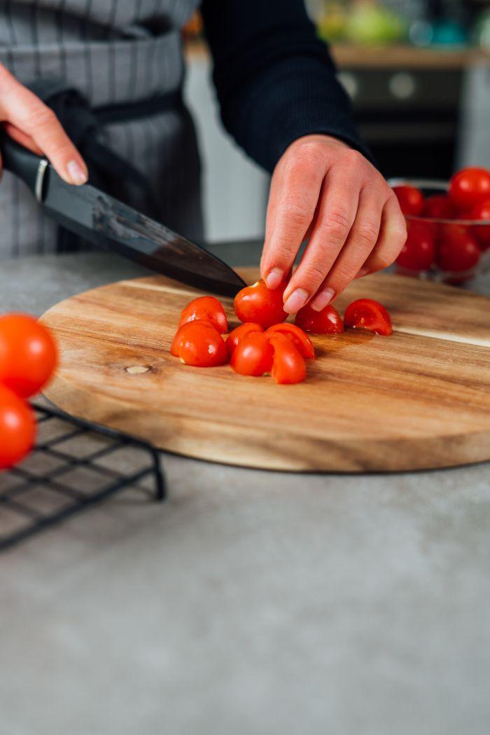 couper tomates cerises en quartiers pour faire la sauce tomate pour spaghetti de légumes, idee que faire avec des courgettes
