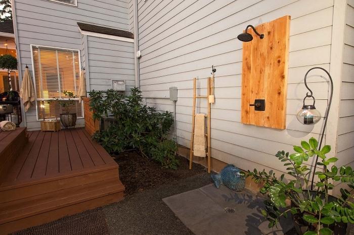 idée décoration de douche d extérieur en métal fixé sur une planche de bois sur bardage panneaux en gris clair