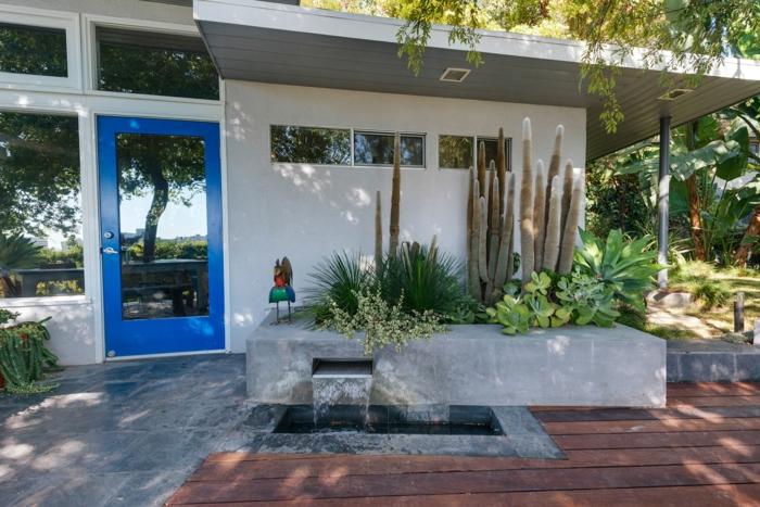 terrasse en bois, cascade et petite piscine, cactus géants, parterre surélevée, espace paysager