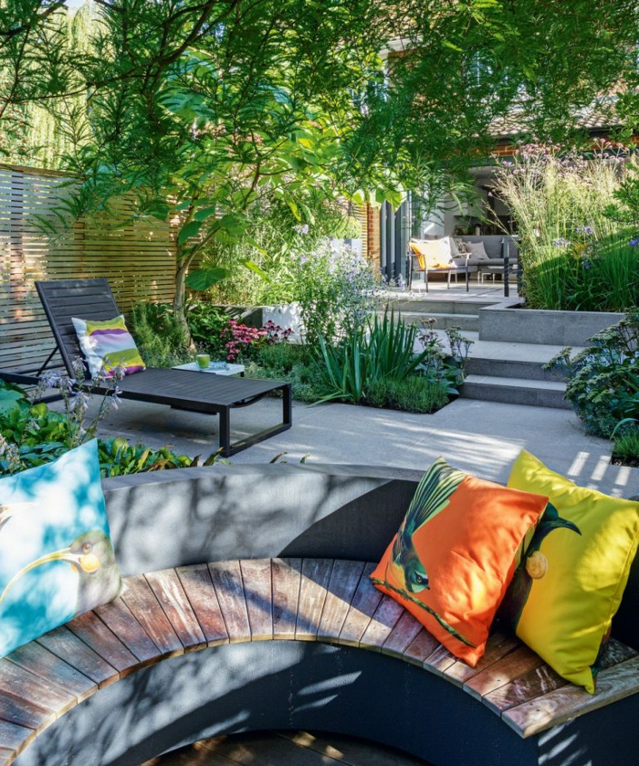 grand espace paysager, chaise-longue noire, salon de jardin, plantes vertes, grand jardin paysager