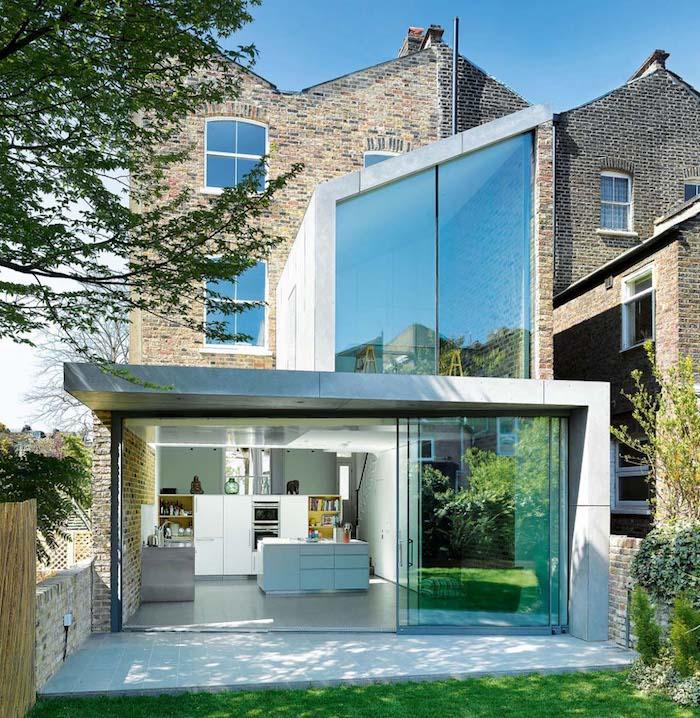 modele extension maison toit plat avec cuisine blanche munie d un ilot central blanc et un évier en béton, verrière, baies vitreées