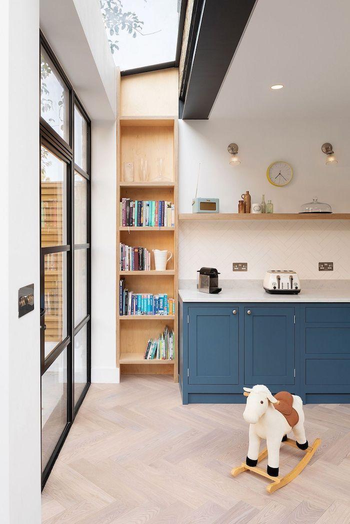 cuisine bleu foncé et bibliotheque d angle à coté d une verrière extérieure industrielle, parquet bois clair, murs blancs, étagère de bois