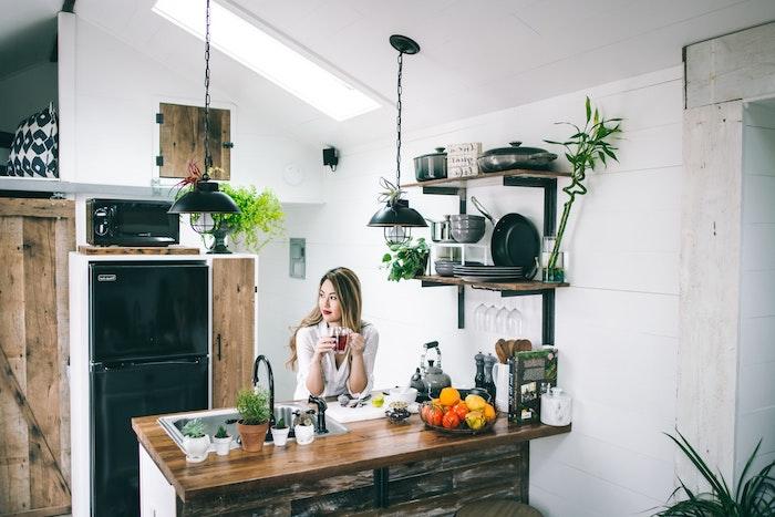motif jungle à travers le mobilier en bois, deco cuisine noir et bois, étagère murale bois et metal, suspensions noires design, petites plantes et herbes en pot