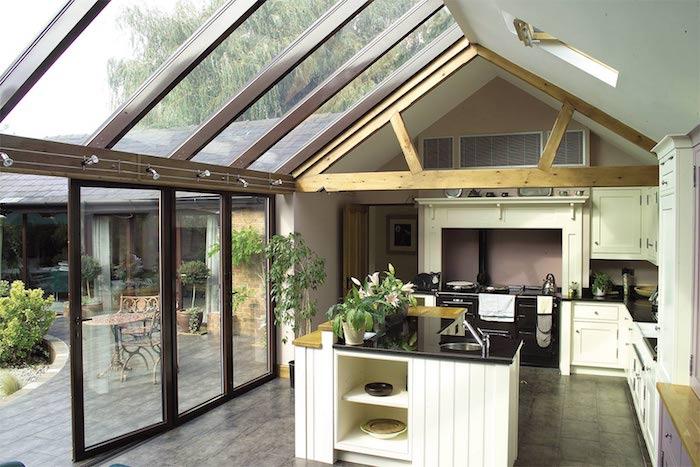 poutres apparentes, fenetres de toit et verrières d une extension maison qui accueillit une cuisine blanche traditionnelle à ilot central et plan de travail noir