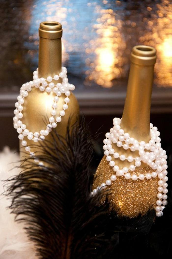 idee repas fete de famille à déco originale, deux bouteilles dorées, colliers blancs, plume noire